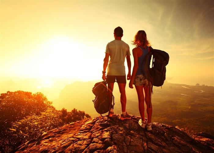 A couple hiking together at sunset