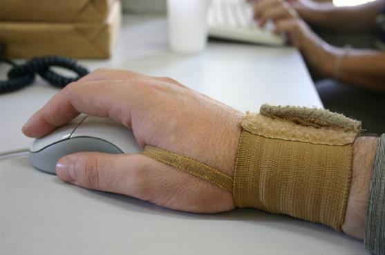 Mans hand on a computer mouse, with a strap around his wrist