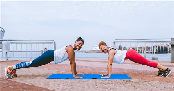 Image of two women doing exercise on a pier